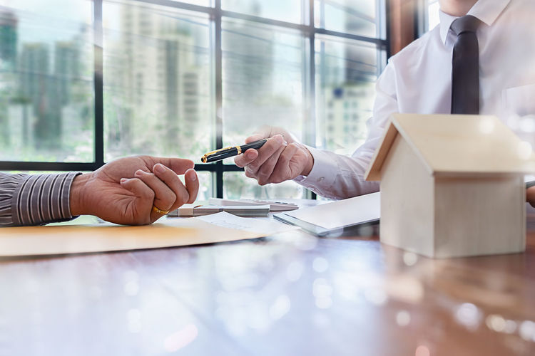 Real Estate Agent Giving Pen To Client At Table In Office