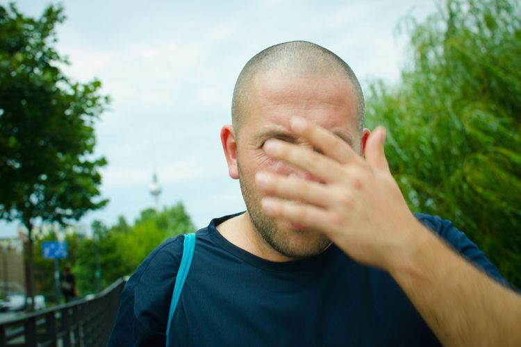 Close-up of man hiding face with hand against sky