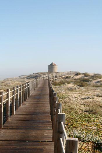 Wooden walkway leading towards castle against clear sky