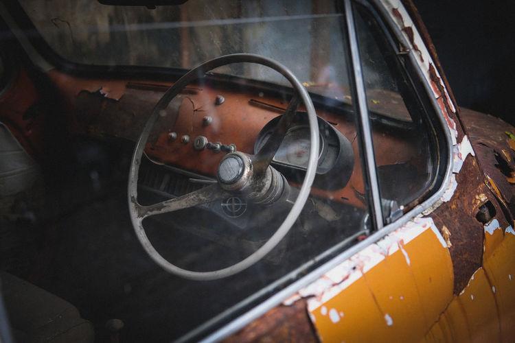 Steering wheel in damaged car seen through window