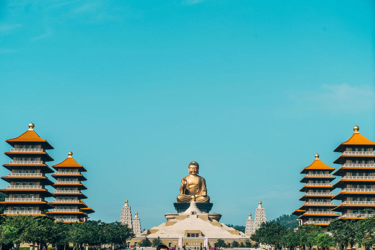 Buddha temple amidst buildings against blue sky