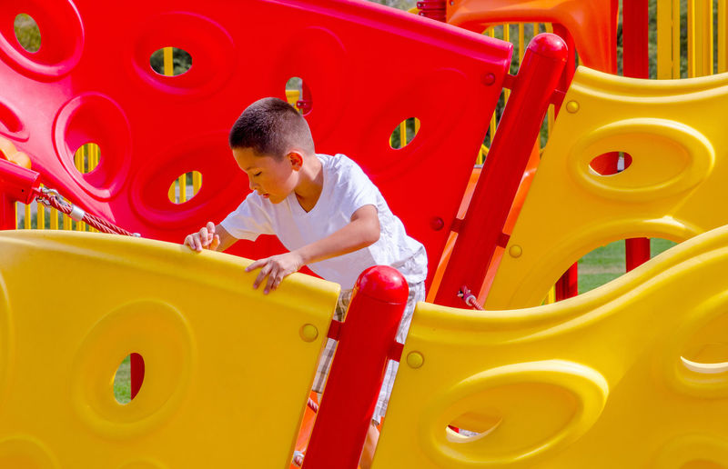 Boy playing on jungle gym at playground