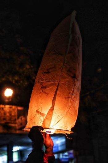 Midsection of person holding illuminated lantern at night