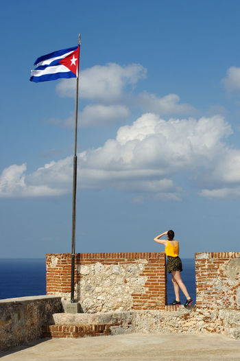 Man standing by flag against sky