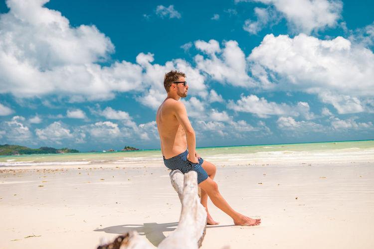 Full length of shirtless man at beach