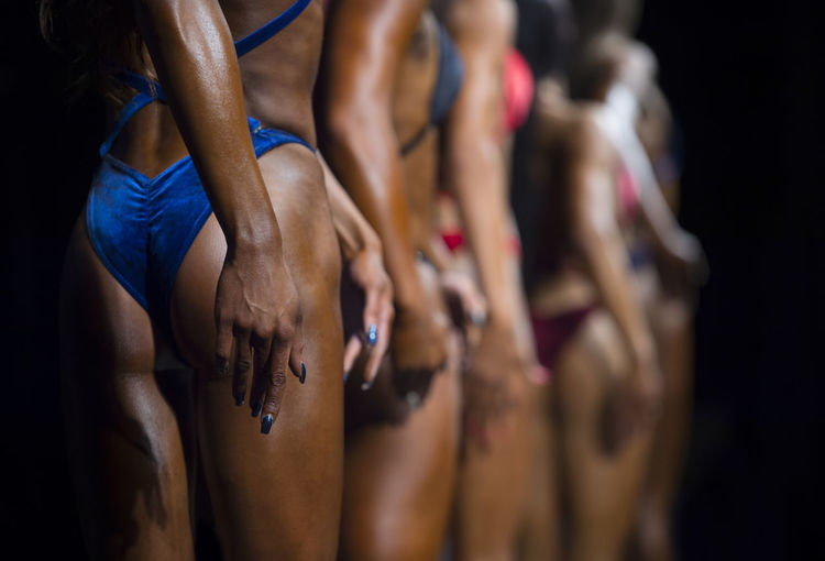 Group Woman in bikini posing. Girl at fitness bikini contest. Impressive female athlete. Beautiful and aesthetic Fitness Fitness Training Clothing Adult Human Body Part Lifestyles Women Young Adult Athlete Group Of People Sports Clothing Indoors  Body Part Midsection People Healthy Lifestyle Togetherness Young Women Side View Exercising Black Background Sport Human Arm Human Limb