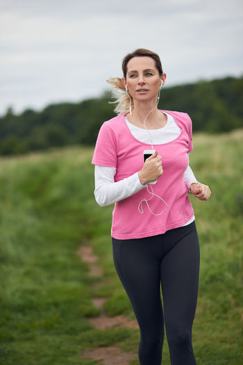Concentrated woman running through field Field Listening Music Running Rural Trailrunning Woman Best Ager Concentrate Concentrated Countryside Cross-country Earbuds Exercising Fitness Jogging Lifestyles Middle-aged Nature Outdoors Portable Information Device Smartphone Sports Sports Clothing Wireless Technology