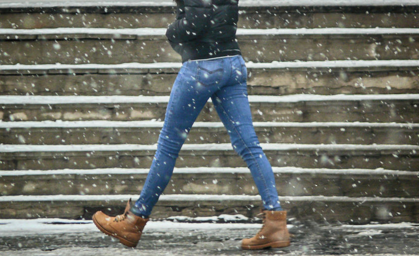 Low section of woman walking on footpath during snowfall