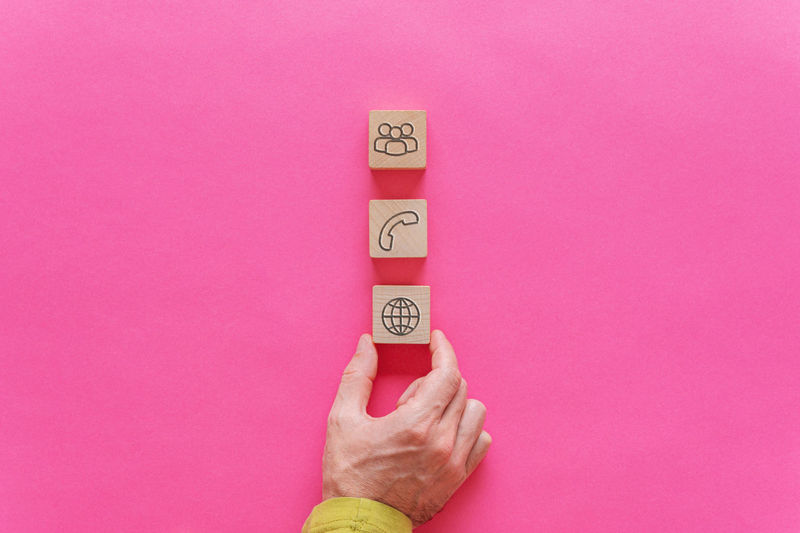 Close-up of hand holding clock against pink background