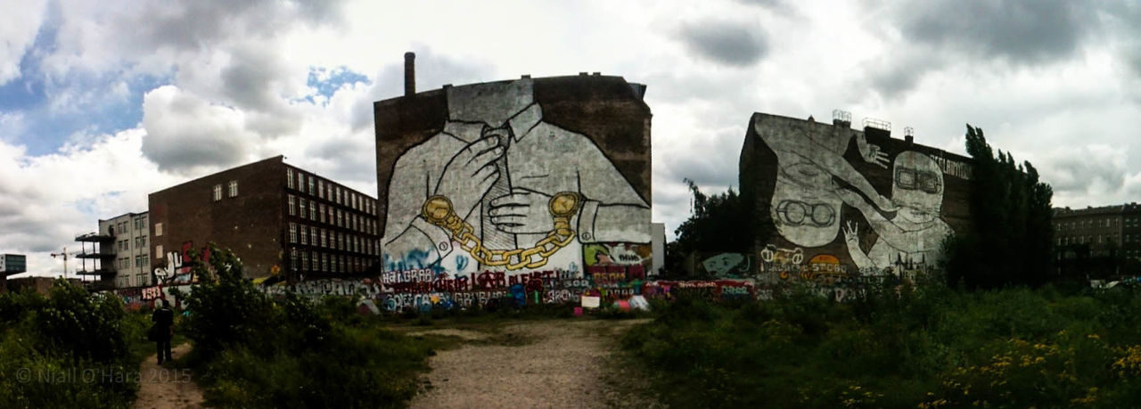Graffiti on wall against cloudy sky