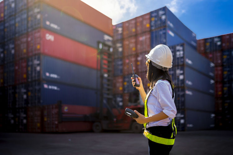 Woman Foreman control loading Containers box from Cargo freight ship for import export. Box Business Container Logistics Transport Work Cargo Communication Control Engineer Export Female Foreman Helmet Import Inspection Loading Occupation Portrait Safety Ship Technology Terminal Wireless Technology Women