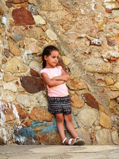 Thoughtful Girl Standing Against Stone Wall