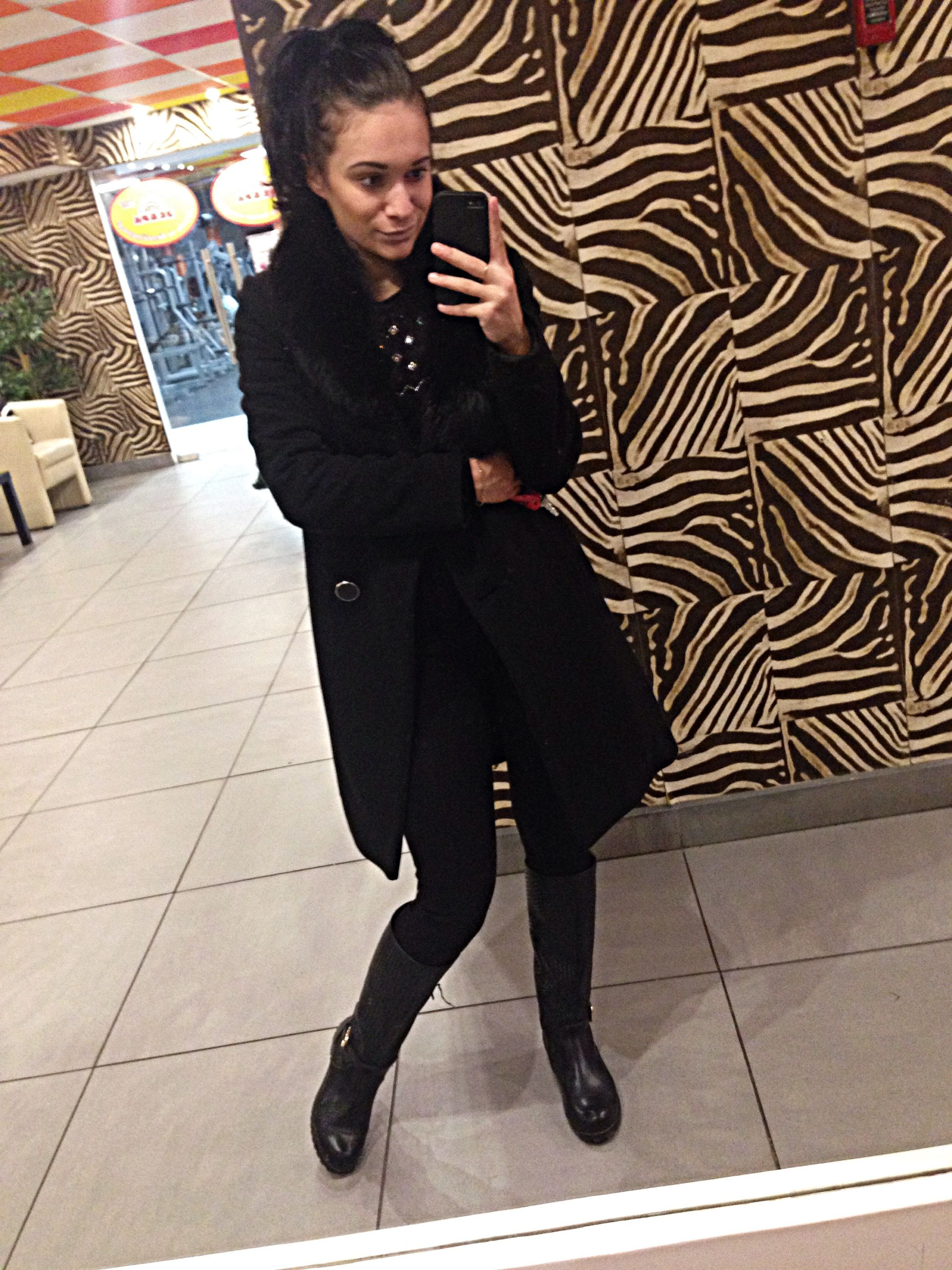 casual clothing, lifestyles, full length, young adult, front view, standing, looking at camera, person, portrait, leisure activity, young women, indoors, wall - building feature, fashion, tiled floor, high angle view, three quarter length, fashionable