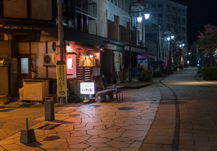 Illuminated street amidst buildings at night
