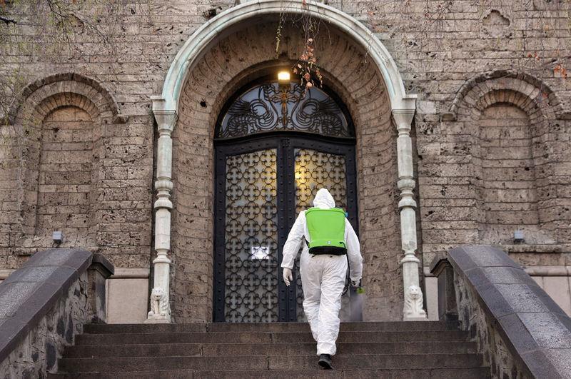 Rear view of man walking in temple outside building