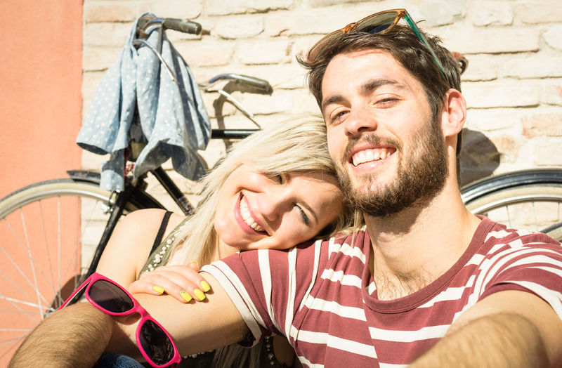 Portrait Of Young Couple Smiling While Sitting Against Bicycle