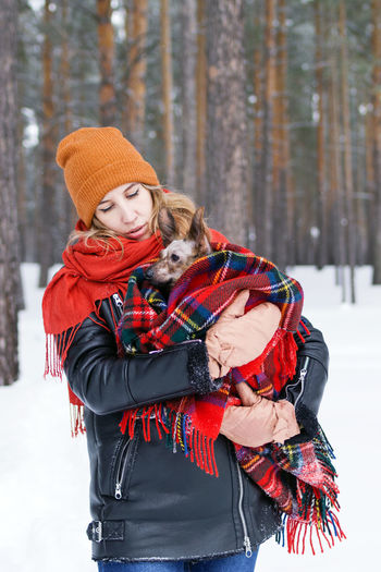 Woman with dog covered in blanket at forest during winter