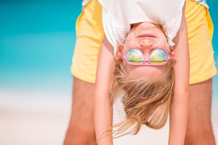 Portrait of woman wearing sunglasses against blue water
