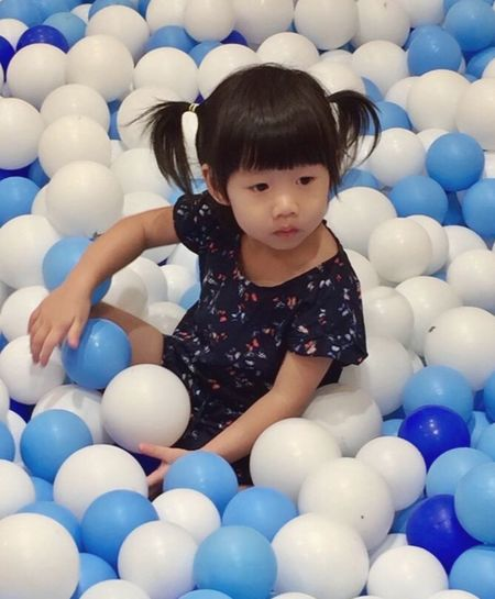Cute girl looking away while sitting in ball pool