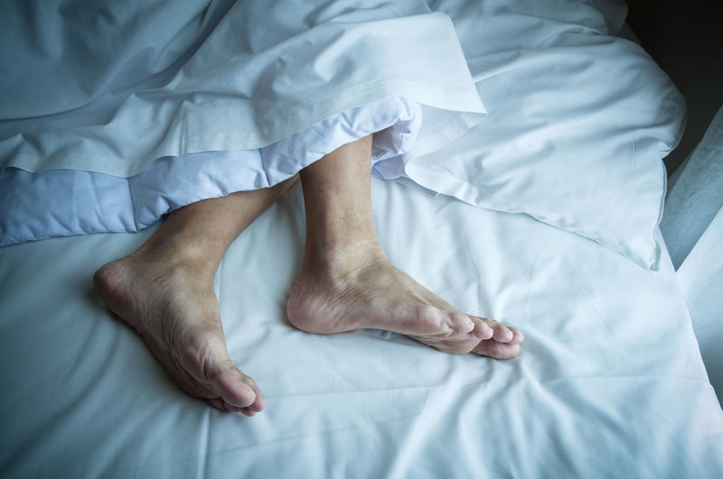 Low section of person lying on bed at home
