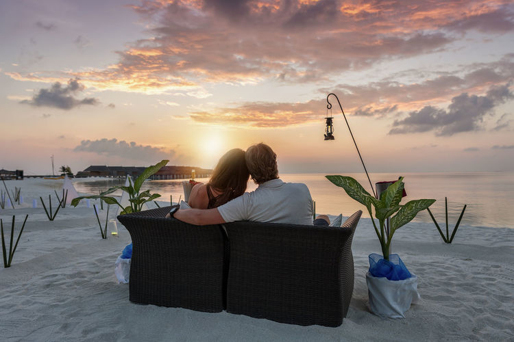 Rear View Of Couple Sitting On Sofa At Beach During Sunset
