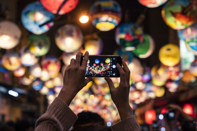 Cropped hands of woman photographing illuminated lanterns at night