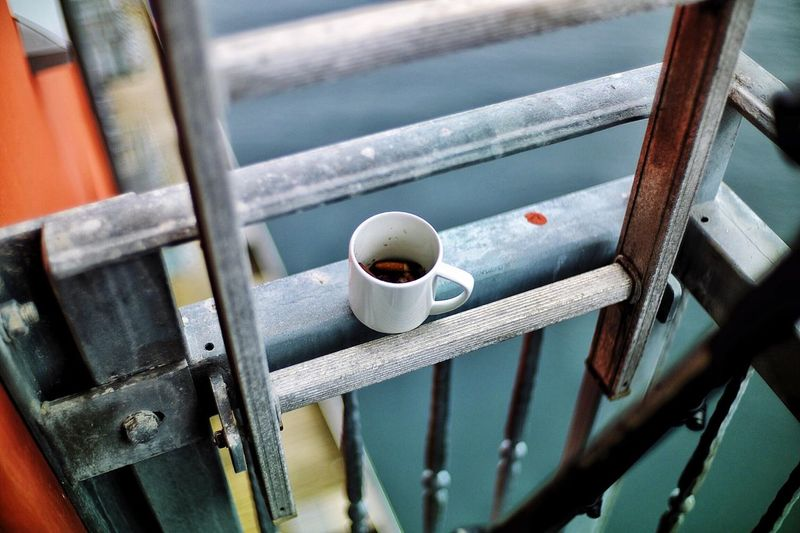 High angle view of cigarette butts in coffee cup on ladder