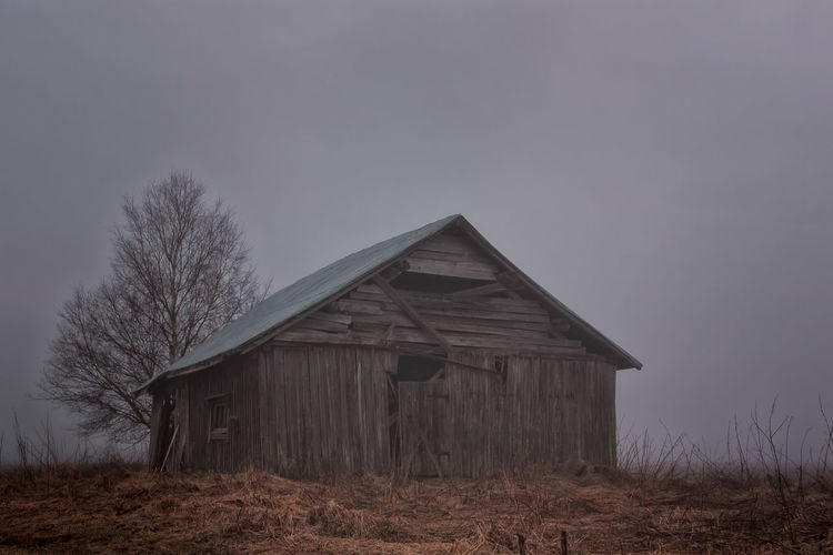 Abandoned barn on field during foggy weather