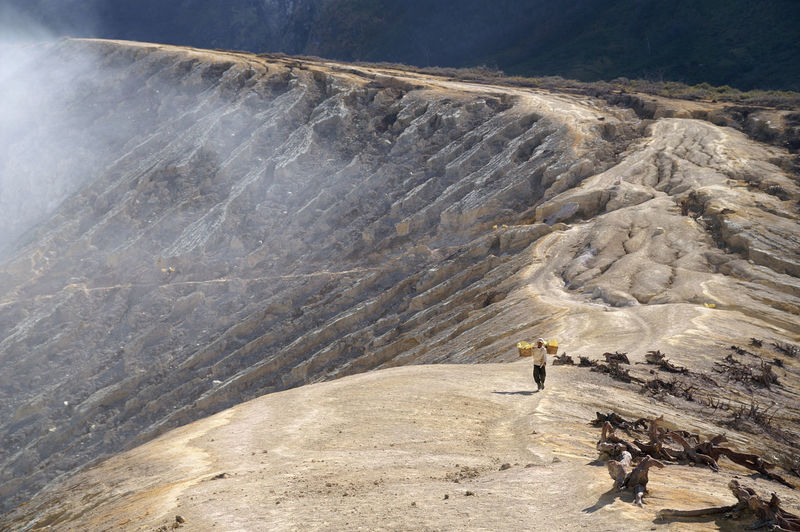 High Angle View Of Man Carrying Sulphur At Ijen Crater