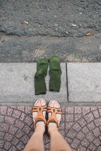 Low section of woman by socks on sidewalk