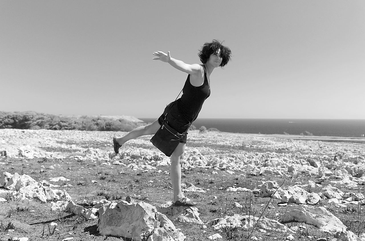 Full Length Of Woman Standing With Arms Outstretched On Rock Against Clear Sky