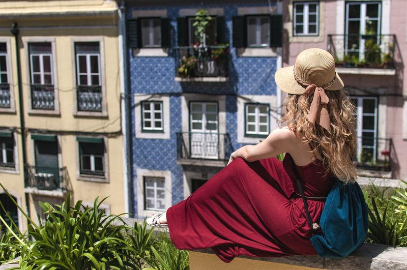 Woman sitting against buildings