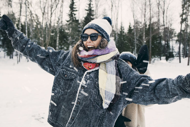 Happy woman enjoying with friend at snowy field