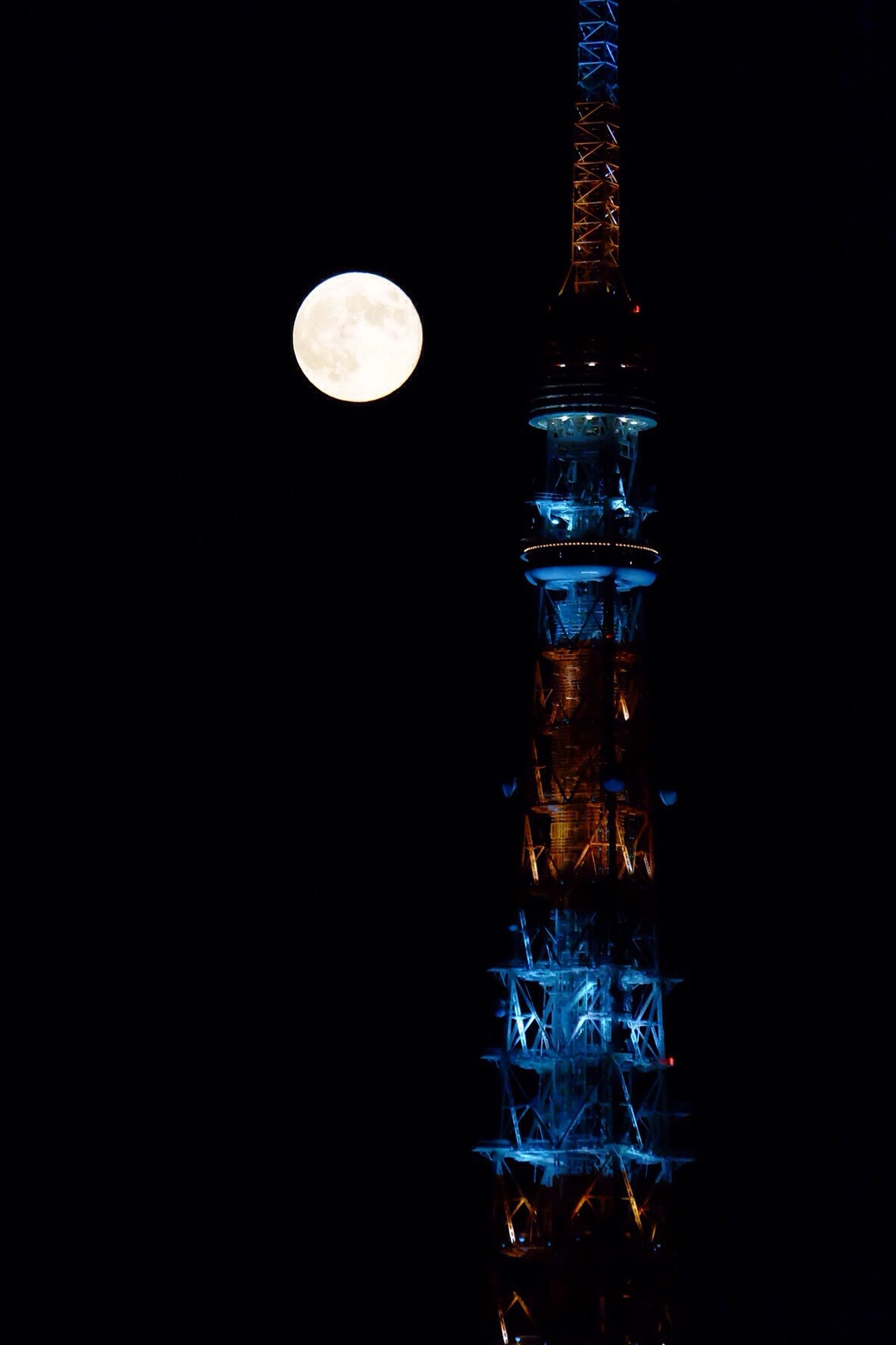 night, illuminated, low angle view, built structure, architecture, dark, copy space, sphere, building exterior, lighting equipment, city, clear sky, moon, sky, glowing, tower, no people, full moon, electricity, light - natural phenomenon
