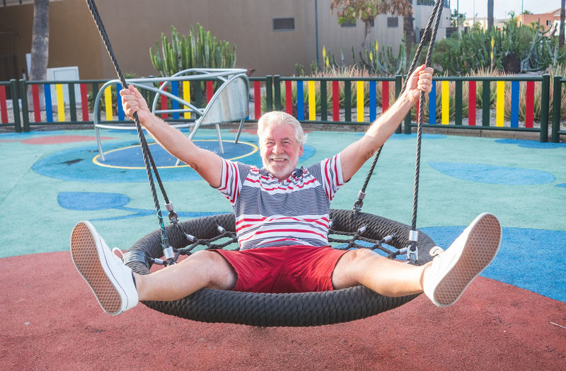 Portrait of happy senior man with arms outstretched sitting on swing