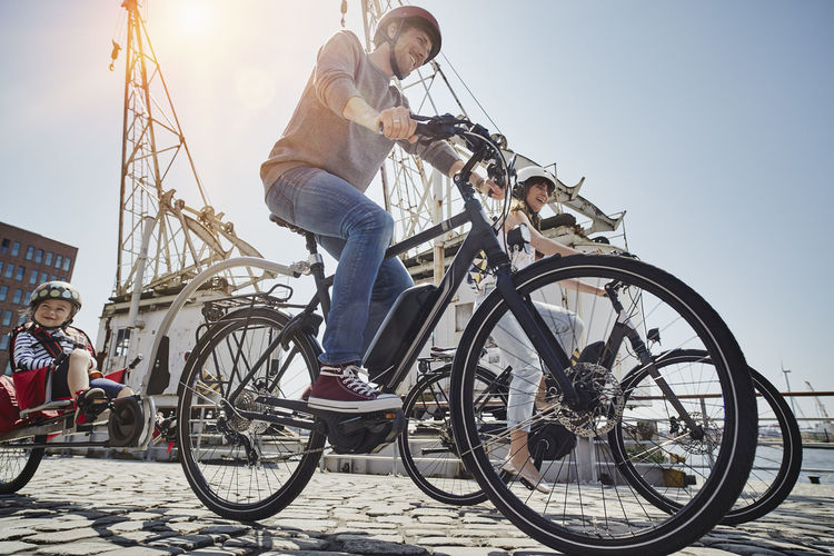 Low angle view of boy riding bicycle against sky