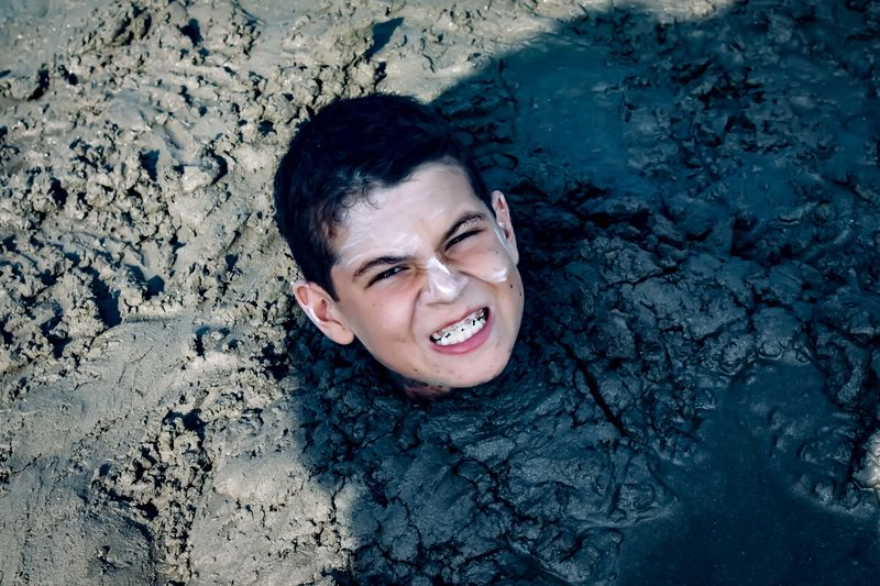 High Angle Portrait Of Teenage Boy Clenching Teeth While Being Buried In Mud