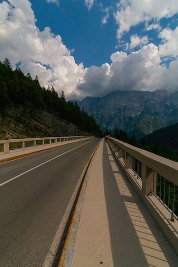 amazing view on the bridge at the predil pass, slovenia/italy EyeEm Best Shots EyeEmNewHere Slovenia Beauty In Nature Cloud - Sky Connection Day Diminishing Perspective Direction Dividing Line Environment Mountain Mountain Range Nature No People Outdoors Plant Railing Road Sign Sky The Way Forward Transportation Tree
