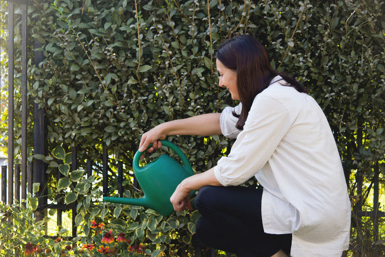 Woman crouching while watering plants