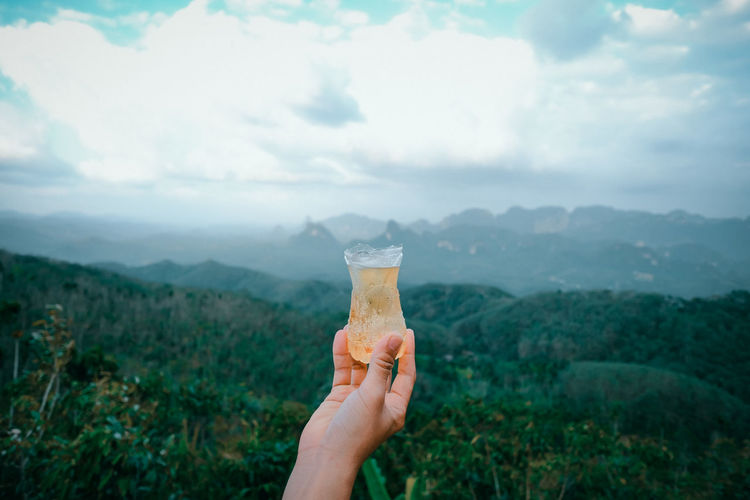Midsection of person holding drink against mountain range