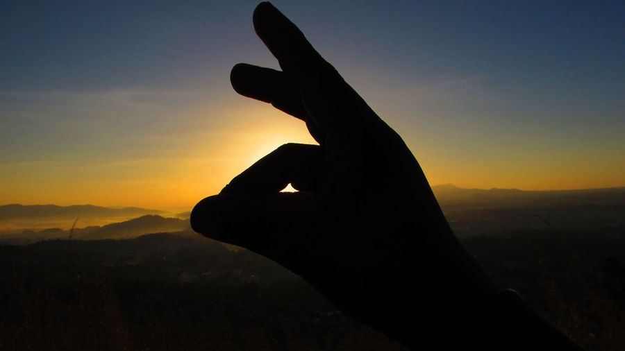 Close-up of silhouette hand against scenic sky