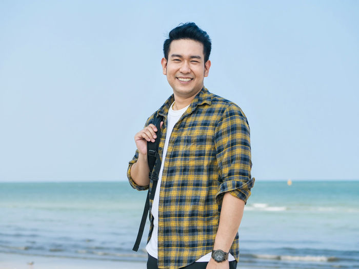 Portrait of smiling man standing at beach