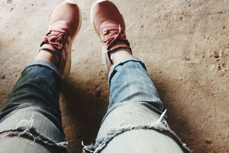 Low section of woman wearing shoes and torn jeans