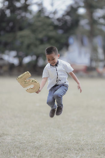 Full length of boy with number 5 balloon in mid-air