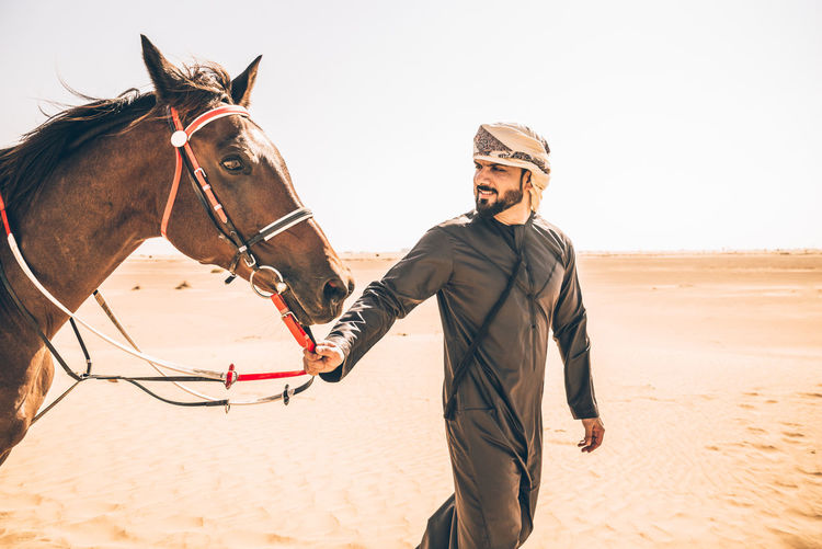 Man with horse walking at desert against clear sky
