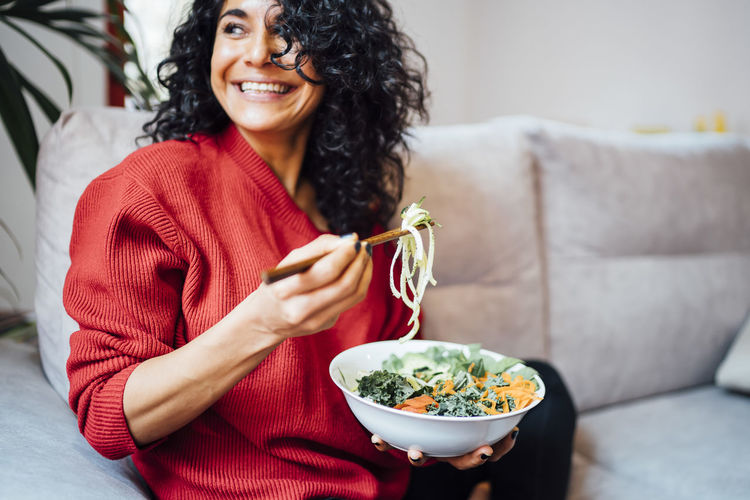 Woman holding food while sitting on sofa
