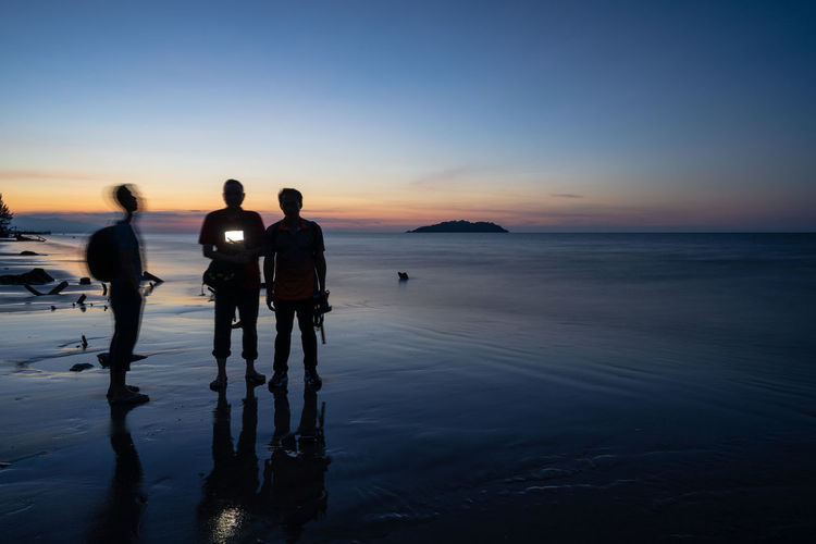 People holding camera while standing at beach during sunset