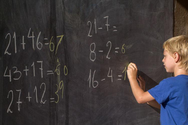 Boy solving mathematics on blackboard