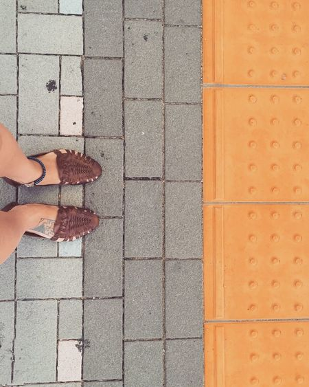 Low section of woman wearing sandals standing on footpath