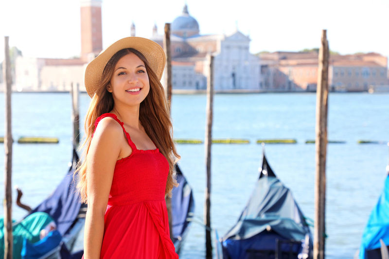 Smiling young woman wearing hat standing by canal